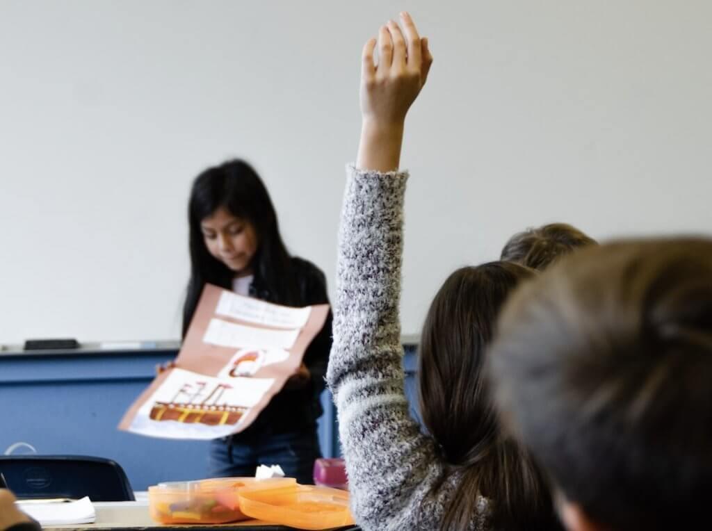 授業中に手を挙げる少女