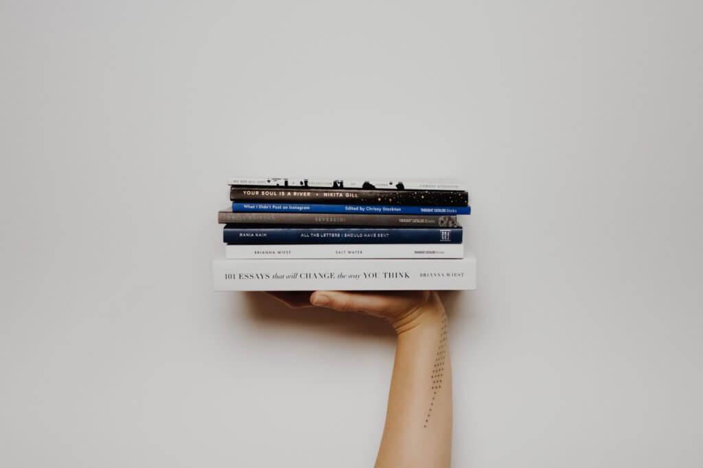 積まれた本を手に持つ